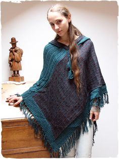 Zelda wool knit poncho #triangular hooded knit #alpaca #unisexponcho. #Fringes on the bottom. The game of braids on the shoulder makes this #alpacaponcho very nice. The #colours of the #geometricdesign are perfectly matched. #Soft and #warm, this #unisex #ponchoalpaca does not go unnoticed #lamamitafashion