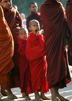 In this photo taken on Saturday, Jan. 26, 2013, a young Buddhist novice monk yawns while lining up to collect alms during an annual pagoda festival in Myanmar's ancient city of Bagan.