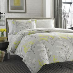A graphic silhouette pattern creates a minimalist urban garden in your bedroom. A cool platinum grey with darker grey accents a mix of white and lemon yellow. A hand-painted geometric trellis pattern in pale grey and white on the reverse.
