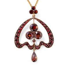 Bohemian Garnet Necklace. An artful combination of disparate design elements - a classic Art Nouveau whiplash motif and a three-leaf clover - coalesce for a striking effect in this enchanting pendant necklace from turn-of-the-century Czechoslovakia, a.k.a. Bohemia. 1 7/8 by 1 5/16 inches, 18 inch chain.