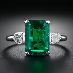 2.77 Carat Emerald and Bullet-Cut Diamond Art Deco Ring: old mine Colombian Emerald, weighing 2.77 carats (but presenting about one carat larger due to its spready cut), is classically showcased in platinum between a shimmering pair of bullet-cut diamonds, together weighing one-half carat. A simply stunning Art Deco jewel, circa 1930s.