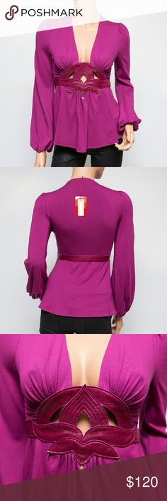 """Ingwa Melero Magenta Jersey Leather Lotus Top New with tags! This is a beautiful magenta-colored jersey Lotus blouse by NYC designers, Ingwa; Melero. It has a genuine leather cut-out in the shape of a lotus flower below the low-cut bust, which is also accented with tiny charms. It has long bishop sleeves, which because of the elastic at the ends, could be pushed up and worn shorter. It is made with 94% rayon and 6% lycra. It measures 21.5"""" long and 15"""" across the chest from under the arm. I…"""