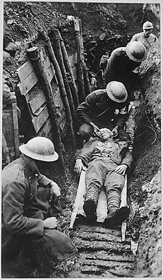 an injured WWI Soldier receiving first aid in the trenches.