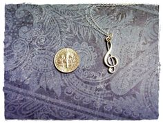 Want! Tiny treble clef necklace.