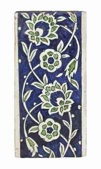 AN INTACT DAMASCUS POTTERY BORDER TILE OTTOMAN SYRIA, CIRCA 1560-1600 Of rectangular form, the blue and green painted decoration with interlocking and scrolling floral tendrils on white ground, minor repainted along the edges, otherwise intact.