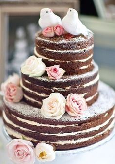 A naked wedding cake showing the thin layers of sponge and buttercream.Decorated elegantly with love birds.