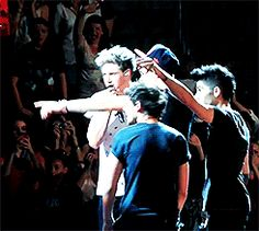 zayn throws something into the crowd and louis gets all cute #partnersincrime (gif)