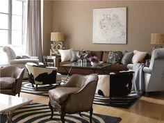 Combinación de sillones y cortinas blancas con paredes topo.