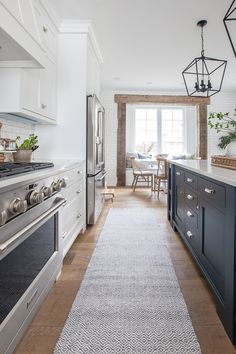 This Blue Note by Benjamin Moore painted island gives a pop of color to this lake house kitchen. Grey Kitchen Island, Navy Kitchen, Gray And White Kitchen, Kitchen Island Decor, Kitchen Reno, Kitchen Remodel, Kitchen Design, Kitchen Islands, Kitchen Ideas