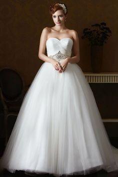 STYLE: GL061          An ethereal ball gown made of Tulle with a fully ruched sweetheart bodice. The natural waist is complimented with an elaborately beaded embellishment and sits over layers of tulle skirt finished with a chapel length train. Available in White, Ivory, or Ivory/Blush. (Shown in Ivory/Blush)