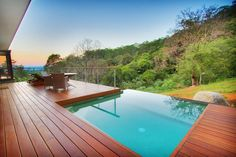 The warm hue of this timber deck partners perfectly with the turquoise drop pool -- what a sight!