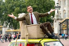 It's been 25 years since Rowan Atkinson first introduced the world to Mr. Bean, and he marked the show's milestone anniversary on Friday with a celebration at Buckingham Palace.  Atkinson rode up to the London landmark in character, atop his famous 1976British Leyland Mini 1000. The arrival recreated a memorable scene from the show, in which Mr. Bean packs his vehicle so full of shopping purchases that he needs to find an alternative way to drive it. http://youtu.be/VjLRTifjpxA]