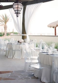 The Resort at Pedregal is a Cabo San Lucas resort and event venue for getaways, gatherings and weddings in Mexico. Stunning beach wedding with ghost chairs. Photo: Lacie Hansen