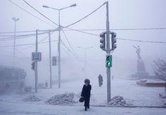 Amos Chapple : photo-reportage à Yakoutsk, surnommée à juste titre la ville la plus froide du monde. Une femme plaque une moufle contre son visage pour le protéger du froid, qui atteint quand même -50 °C. En fond on voit une statue gelée de Lénine surplombant la place centrale de la ville.