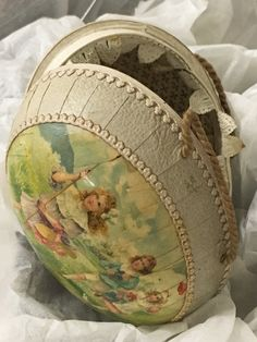hinged egg-shaped container with paper hinge and string carry handles on each half, exterior features glued image and sewn border, interior is paper-lined in white with gold fleur-de-lis pattern and includes edging of paper lace on one half Museum no. Collection Manager, Memorial Museum, Paper Lace, Auckland, Easter Eggs, Coin Purse, Container, Exterior, War