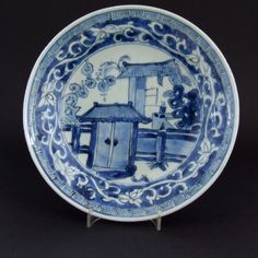 A Ming Blue and White Ko-Sometsuke Porcelain Dish, Tianqi (1621-1627) or Chongzhen (1627-1644). Decorated with a Door Leading into a Court Yard with a Scholar Desk (a Brushpot is on the table) a Scholar`s Rock and Banana Plants. The Cavetto Painted with a Meandering Lotus Scroll in White Against a Blue Background. The Rim with a `Greek Key` Border.