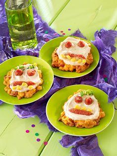 Kleine pikante Brandteig-Taler mit gruseligen Gesichtern aus Salami und Mais