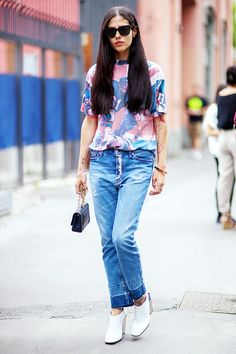 A graphic, printed t-shirt is worn with distressed jeans and cool white pumps and a mini bag
