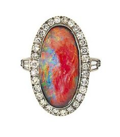 An opal and diamond cluster ring   The oval cabochon black opal within a brilliant-cut diamond surround, between tapered baguette and brilliant-cut diamond shoulders