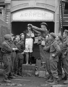 Lance-Corporal E.C. Crook of The Perth Regiment adjusting the hat of a mannequin, Arnhem, Netherlands, 15 April 1945. April 15, 1945. Library and Archives Canada MIKAN 3214469