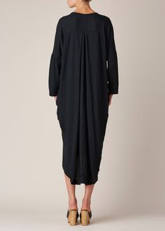 Light wool dress with pleated back yoke in forest green. Side seam pockets. Loose, oversize fit. Dropped shoulders with cropped long sleeves. Dry clean or hand wash cold.