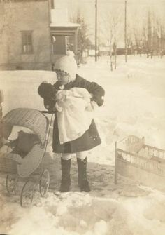 "Old Vintage Photo Little Girl plays with Doll outside in blustery winter afternoon with her beloved doll. circa 1900. A second in time ""frozen"" for eternity."