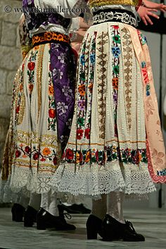 Croatian folk-dress (lace and embroidery showing at back of skirts, not covered by aprons)