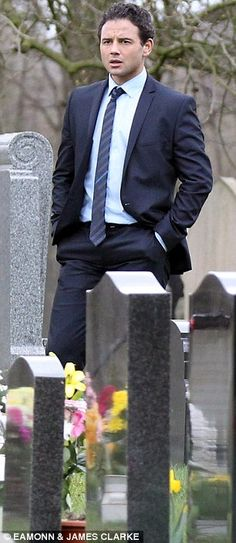 Suitably styled: Jason (played by Ryan Thomas) is dressed in a slim-fitting navy suit for the sombre occasion. His face is evidently pained as he stares at his relative's grave from afar