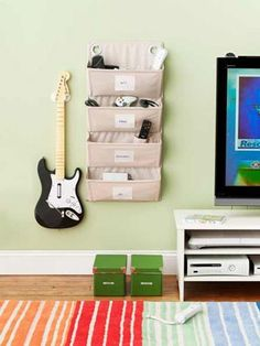 To separate controllers from other media-room remotes (and get them out from underfoot), hang a canvas organizer with designated pockets. (Instruct gamers to loosely fold cords instead of winding them tightly, so as to avoid damaging the cords insulation.) /Kitchen hooks designed for brooms can hold video game guitars.