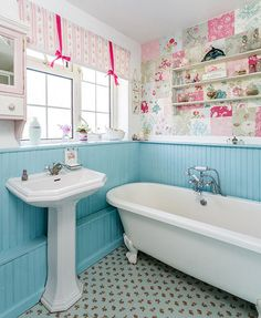 patchwork wallpaper and blue backed board. Floral bathroom tiles and a claw foot tub