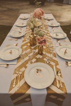 "DIY table runner and centerpieces:   ""We spray painted little animals with gold paint, hand stamped our guests' names onto shipping tags and then tied each tag to the animal with gray baker's twine. I thought they turned out super cute. We even took hand-sewn muslin and spray painted it in different patterns with gold paint to make the table runners."""