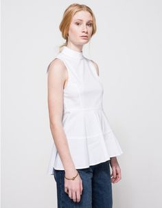 A lightweight classic sleeveless top in White from Farrow.  Features stand collar, wide straps, short invisible zipper back, structured bodice, elastic waistline, wide flare hem, high-low hem and fitted cut.  •Lightweight sleeveless top in White •Sta