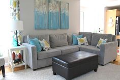 Grey couch. Love the punches of color. The three paintings would be easy to recreate.