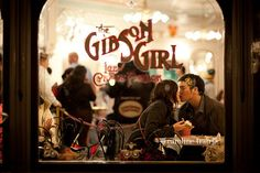 Looking through the front window of the Gibson Girl Ice Cream Shop on Main Street, USA... A special moment captured (Disneyland Engagement Photos)....