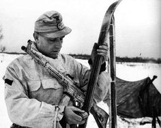 A German soldier of the 1. Skijäger-Division, armed with a StG 44, prepares his skis. Ukraine, 1944.