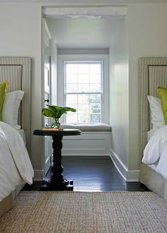 Bedroom with taupe ticking stripe twin headboards with French brass tacks trim, lime green pillows, jute rug and built-in window seat.