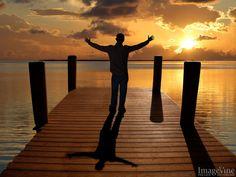 man worshiping God at sunset