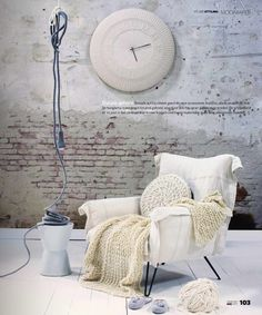 the white brick wall / an arm chair & wonderful knitted pillow and blanket / scandinavian style / clock / lighting / living room or bedroom