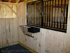 Interior of Horse Barn showing stall with oak kickboard, feeder, and grill in partition opening into tack room in pine board and batten shed with oak post and beam construction--Amish made and available in California http://www.backyardunlimited.com/