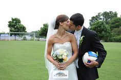 Bride and groom kissing with a soccer ball.