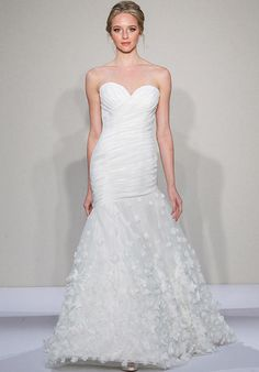 Ivory strapless fit-and-flare with a ruched organza bodice featuring a sweetheart neckline and an asymmetrical drop waist tulle skirt with silk flower applique | Dennis Basso for Kleinfeld | https://www.theknot.com/fashion/14084-dennis-basso-for-kleinfeld-wedding-dress