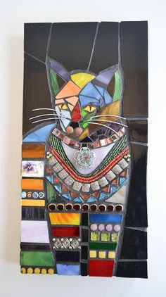 Cat with Golden Eyes by Lisa Fields Clark 12 x 6 x 7/8 Indoor Mosaic Wall Hanging. An original design set on a sanded, painted, and sealed pine wood panel with screws and wire installed on the back for hanging. All the stained glass used to create this piece is hand-cut. The cat is