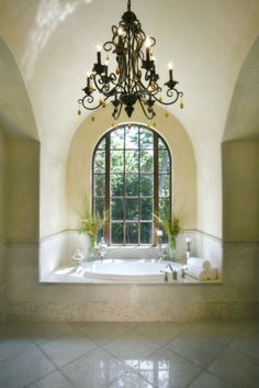 A tranquil oval tub is set into a nook with a large arched window, with an ornate chandelier overhead