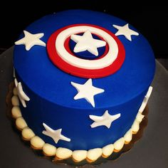 Blue buttercream iced cake with white fondant stars and fondant captain america topper. by sugarandfrosting.com