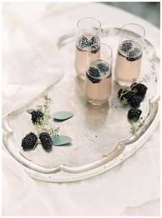 Champagne cocktails with blackberries on a vintage silver tray. Image by Allison Kuhn Photography.