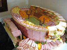 Super Bowl Stadium made out of a jaw-dropping wall of triple-decker sandwiches, ham slabs & pepperoni coins surrounding seat sections stockpiled with pretzels, corn chips & miniature blocks of yellow & white cheese! WOW now that's a deli platter!!