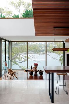 This waterfront home designed by TKD Architects embraces the Japanese and Australian cultural heritages of the owners, as well as their love of Bali. The living room is down a couple of steps from the kitchen and features a Han J. Wegner 'CH28' chair and Gubi 'Grasshopper' lamp both from Cult. The timber table was custom made in Byron Bay.