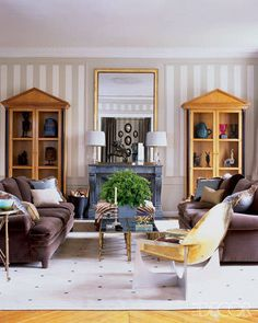 In the living room, a pair of Lucite lamps from Galerie Chahan and an 18th-century French overmantel mirror; the neoclassical cabinets are 1940s.   - ELLEDecor.com