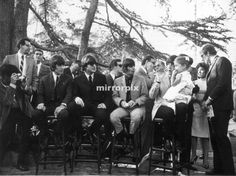 The Beatles attend a reception organized by the Foundation against hemophilia at the Livingston Garden, Los Angeles, 24th August 1964. Paul McCartney holds Rebel Lee Robinson (daughter of Edward G. Robinson) in his arms.
