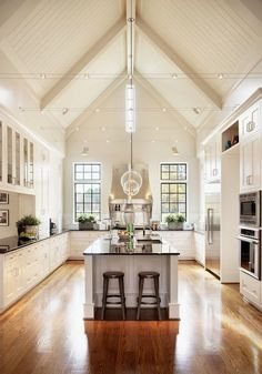 Get the look : Caviar Single Pendants in polished nickel hanging in a row over the kitchen island. LOVE those high ceilings!